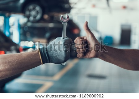 Close-up Thumb Up and Mechanics Hand with Tool. Automobile Master Wearing Gloves Showing Positive Gesture after Finishing Work. Technic occupation. Automobile Repair Service Concept. #1169000902
