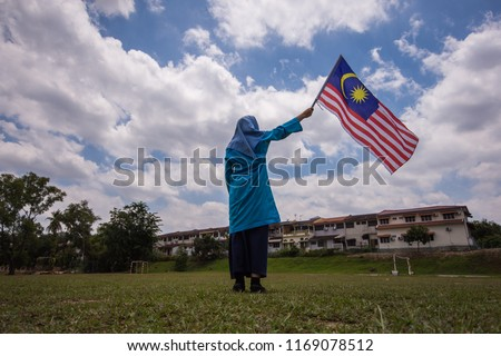 Girl waving the Malaysia Flag. Independence Day & Merdeka Concept. Blue sky and copy space. #1169078512