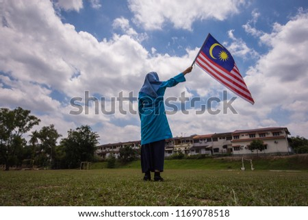 Girl waving the Malaysia Flag. Independence Day & Merdeka Concept. Blue sky and copy space. #1169078518