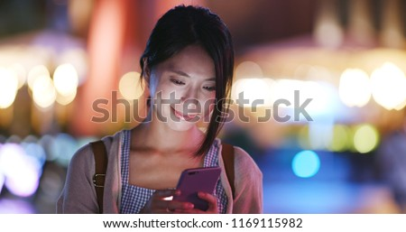 Woman use of cellphone in the city in the evening #1169115982
