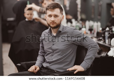 Barbershop Man in barber chair expects hairdresser styling #1169156608