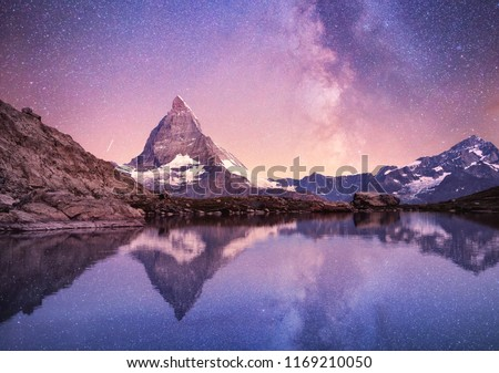 Matterhorn and reflection on the water surface at the night time. Milky way above Matterhorn, Switzerland. Beautiful natural landscape in the Switzerland #1169210050