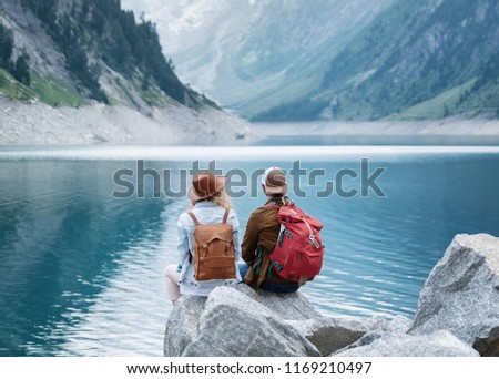 Travelers couple look at the mountain lake. Travel and active life concept with team. Adventure and travel in the mountains region in the Austria #1169210497