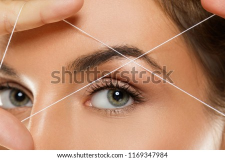 Close-up of female eye with a thread. Eyebrow threading - epilation procedure for brow shape correction Royalty-Free Stock Photo #1169347984