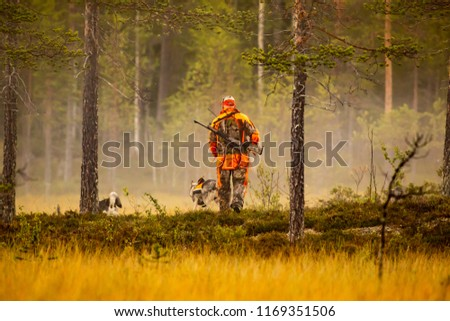 Hunter and hunting dogs chasing in the wilderness #1169351506