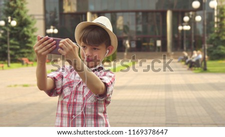 Handsome little boy taking a selfie on his cellphone oudoors. Attractive brunette kid choosing better background for photo. Caucasian male child in hat looking into the smartphone camera