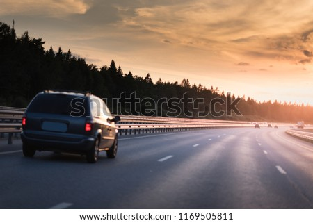 Car and light on the road. Sunset on the evening highway with metal safety barrier #1169505811