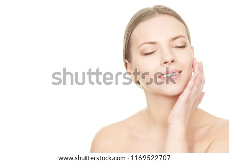 Deep skincare. Beautiful young woman moisturizing her skin. Applying cream to her face. Attractive female massaging her face with her eyes closed copyspace #1169522707