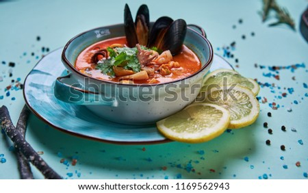 seafood soup in a blue plate #1169562943