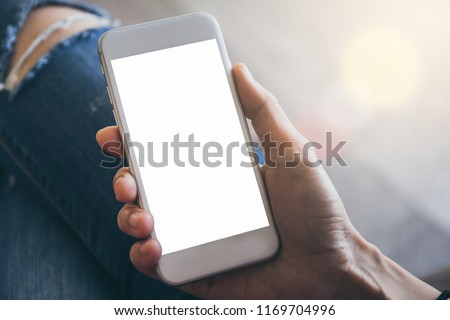 Mockup image of woman's hand holding and using white mobile phone at outdoor with copy space,blank screen for text.concept for business,people communication,technology electronic device. modern life s #1169704996