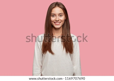 Isolated shot of pleasant looking cheerful brunette youngster has appealing look, healthy skin, dressed in casual white sweatshirt, poses against pink studio wall. Happiness and lifestyle concept #1169707690