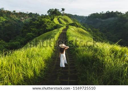 Young beautiful woman walking on Campuhan Ridge way of artists, in Bali, Ubud. Beautiful calm sunny morning #1169725510