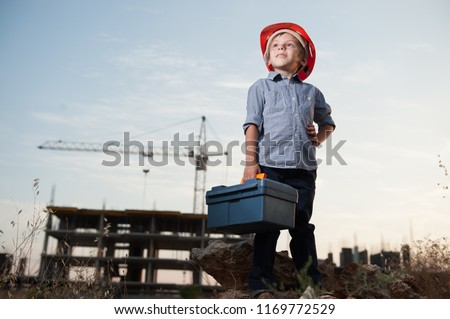cute little kid in builder helmet with toolbox in hand on standing construction site #1169772529
