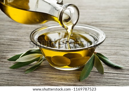 Bottle of Olive oil pouring in a glass bowl with olives #1169787523