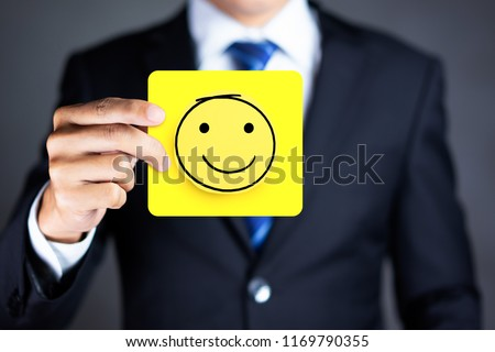 Businessman hold a happy face icon drawn on paper, Customer experience and satisfaction survey concept #1169790355