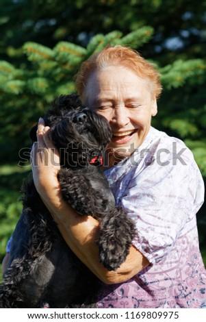 Portrait of an elderly woman hugging black dog Zwergschnauzer #1169809975