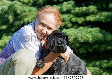 Portrait of an elderly woman hugging black dog Zwergschnauzer #1169809978