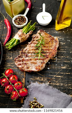 Fresh grilled meat. Grilled beef steak medium rare on wooden cutting board. Top view. #1169821456