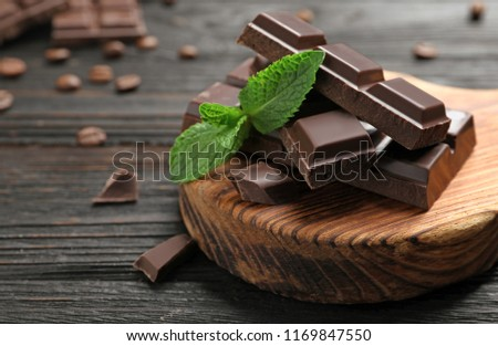 Pieces of dark chocolate with mint on wooden table #1169847550