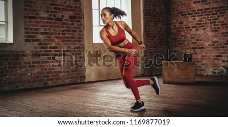 Woman with muscular body exercising at fitness studio. Determined woman during fitness training at gym. #1169877019