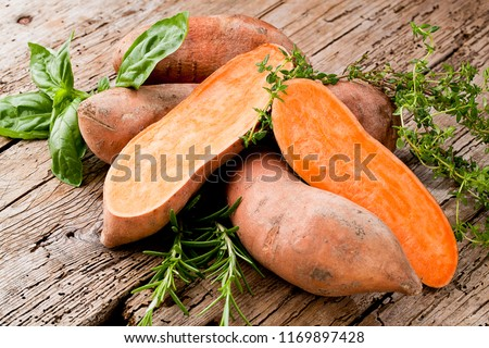 Sweet potato on Wooden background  Royalty-Free Stock Photo #1169897428