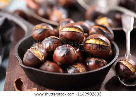 Roasted chestnuts served in chestnut pan on an old table  #1169902603