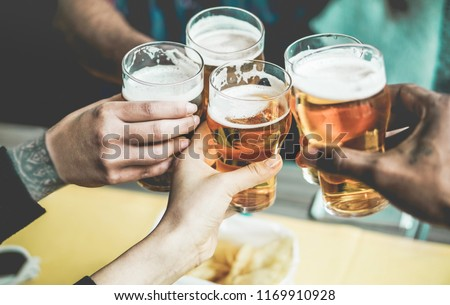 Group of friends enjoying a beer in brewery pub - Young people hands cheering at bar restaurant - Friendship and youth concept - Main focus on left bottom hands #1169910928