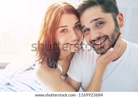 Beautiful young stylish couple in love are hugging each other and enjoying the time spent together in bedroom at home. Love concept and St. Valentines day. Relationships and family #1169923684