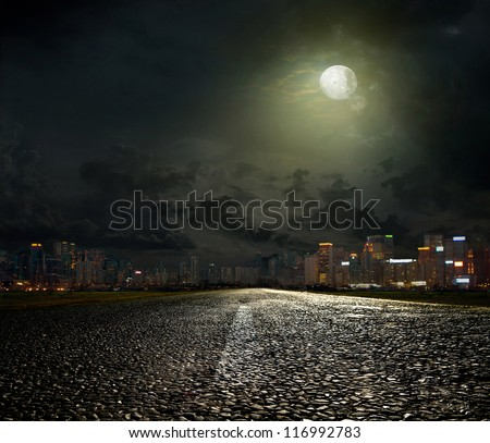 asphalt road leading into the city at night #116992783