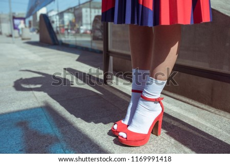 Young woman wearing stylish red skirt and shoes on an urban sidewalk. Low angle view of her shapely legs. Selective focus #1169991418