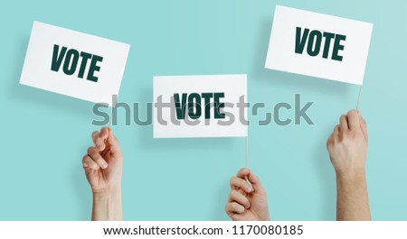 Hands raise the white flags with the word VOTE up. The concept of voting, making choices. Presidential and parliamentary elections. Calling for voting, democracy. #1170080185