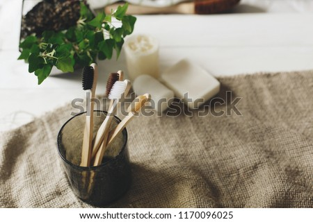 eco natural bamboo toothbrushes in glass on rustic background with greenery. sustainable lifestyle concept. zero waste home. bathroom essentials, plastic free items Royalty-Free Stock Photo #1170096025