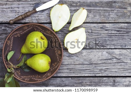 pears in a plate and slices of pears top view. wooden background with pears. ripe organic pears close-up. #1170098959
