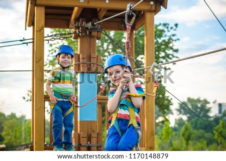 Happy children having fun in adventure park. Two adventurous healthy preschool boys, twin brothers enjoying active day outdoors climbing on the trees. Friendship and brotherhood concept. #1170148879