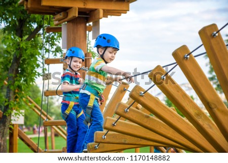 Young boy playing and having fun doing activities outdoors. Happiness and happy childhood concept. Boy swing on rope. #1170148882