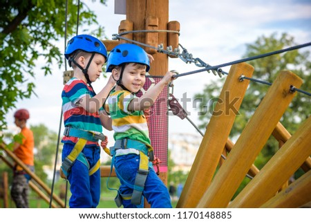 Young boy playing and having fun doing activities outdoors. Happiness and happy childhood concept. Boy swing on rope. #1170148885