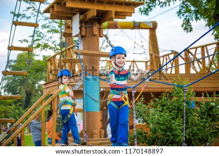 Twin brothers in helmet walks by rope at park sunny summer day in adventure playground. Active healthy leisure time spending concept with children. #1170148897