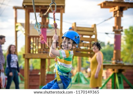 Little cute boy enjoying activity in a climbing adventure park on a summer sunny day. toddler climbing in a rope playground structure. Safe Climbing extreme sport with helmet and Carabiner. insurance #1170149365