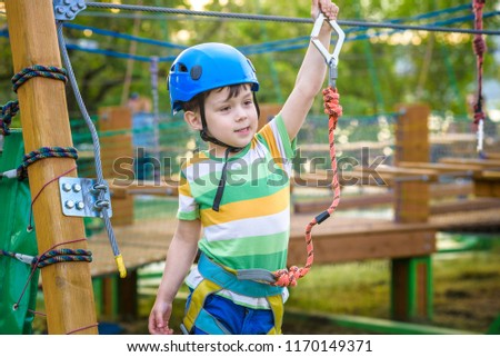 Little cute boy enjoying activity in a climbing adventure park on a summer sunny day. toddler climbing in a rope playground structure. Safe Climbing extreme sport with helmet and Carabiner. insurance #1170149371