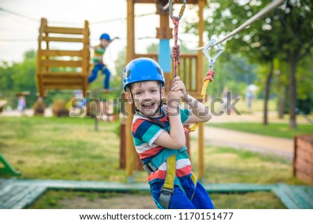 Young boy playing and having fun doing activities outdoors. Happiness and happy childhood concept. Boy swing on rope. #1170151477