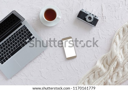 Top view of white office desk with laptop, cup of tea, vintage photo camera and smartphone with isolated screen. Free space for text, business office flat lay concept #1170161779