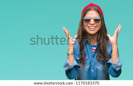 Young beautiful arab woman wearing sunglasses over isolated background celebrating mad and crazy for success with arms raised and closed eyes screaming excited. Winner concept #1170183370