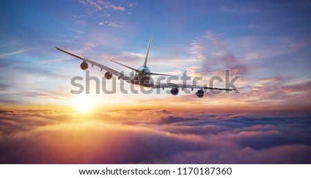 Huge two-storey passengers commercial airplane flying above clouds in sunset light. Concept of fast travel, holidays and business. #1170187360
