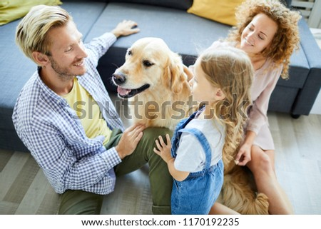 Young family of three sitting on the floor by sofa, talking and playing with pet #1170192235