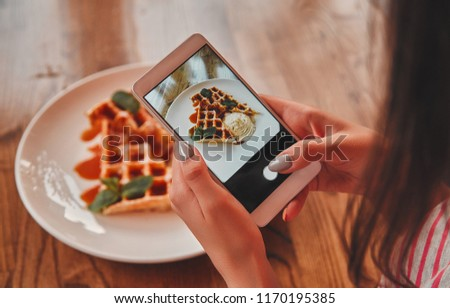 Beautiful young girl is taking pictures of a dessert on the phone while relaxing in a cozy cafe, close-up