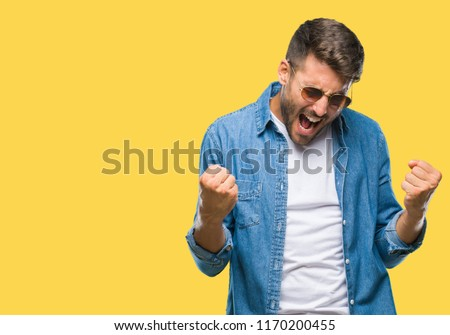 Young handsome man wearing sunglasses over isolated background very happy and excited doing winner gesture with arms raised, smiling and screaming for success. Celebration concept. #1170200455