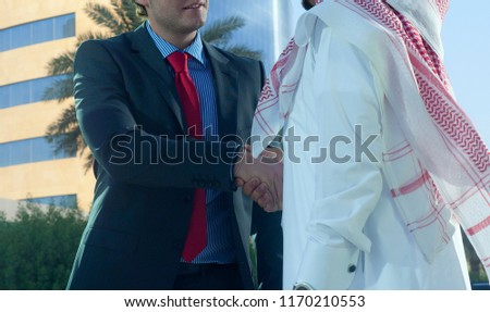 Middle eastern and caucasian businessmen shaking hands outdoor on a sunny day #1170210553