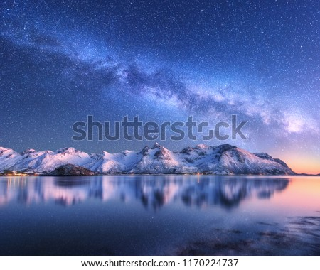 Bright Milky Way over snow covered mountains and sea at night in winter in Norway. Landscape with snowy rocks, starry sky, reflection in water, fjord. Lofoten Islands. Space. Beautiful milky way #1170224737