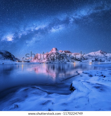 Milky Way above frozen sea coast and snow covered mountains in winter at night in Lofoten Islands, Norway. Arctic landscape with blue starry sky,  water, ice, snowy rocks, milky way. Beautiful space #1170224749