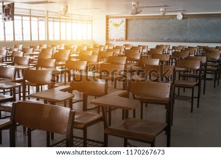 Empty school classroom with many wooden chairs. Wooden chairs in classroom. Wooden arranged in classroom. Empty classroom with vintage tone wooden chairs. Back to school concept. #1170267673